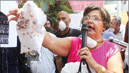 Moradora mostra os resíduos do material e da poeira inalados pela população local. Foto: Clarice Castro